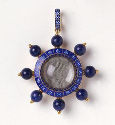 An enamelled and lapiz lazuli gold pendant locket  by Carlo Giuliano,   of circular form, enamelled blue and white with seven   emanating lapiz lazuli beads   London, circa 1890