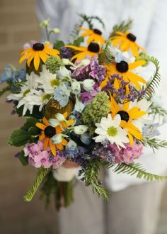 Gorgeous wildflower wedding bouquet. Perfect for an outdoor or barn venue. Designed with black eyed susans, delphinium, daisies, flox, and plenty of garden textures. By Backyard Garden Florist.
