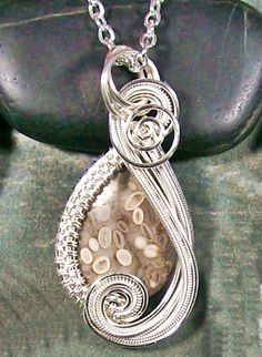 This beautiful wire-wrapped pendant was made of sculpted Sterling silver-filled wire, draped in lovely hand-woven accents, as it cradles a