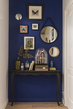 Le couloir peut aussi être conçu comme un minisalon. Un bel aplat de couleur sombre, en contraste avec des murs blancs, apporte profondeur et intimité. La couleur est reprise en écho au sol, comme un tapis. #leroymerlin #ideedeco #madecoamoi #deco #miroir #bleu #blue #entree #hall