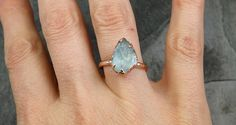 rough and uncut Aquamarine Solitaire Ring Wedding Ring Custom One Of a Kind Gemstone Ring Bespoke Three stone Ring byAngeline  Aquamarine surrounded in recycled 14k rose gold. I hand carved this ring in wax and cast it in solid 14k rose gold using the lost wax casting process. This one of a kind raw gemstone ring is a size 7 1/4 it can be resized. The aquamarine stone measures about 12mm X 8mm. Throughout all time and history, in every tribe and culture all around the world crystals mine...