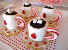 Marshmallow coffee mugs with cookie under as the saucer and candy cane handle