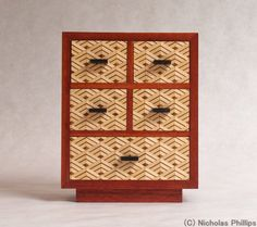 A beautiful piece for your shelf or mantle. Or on your dresser to hold your favorite jewelry. This five drawer mini Tansu stands 7-1/2 tall and is 6 wide. The drawers are decorated with Japanese-style Yosegizaiku, which I make in my shop. The case is Bloodwood. Extra care has been taken when making the case to have the grain of the Bloodwood wrap completely around the case. Ive used Shellac to bring out the color and depth of the wood. The drawer pulls are Ebony. Even though the drawers ...