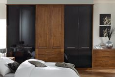 Bold, black high-gloss wardrobes are the dominating feature of this bedroom design.