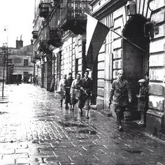 "August 1st 1944, Warsaw, Casimir The Great Square, insurgents of ""Pięść"" battalion on patrol.  Source: Wikimedia Commons.  Photo by Stefan Bałuk."