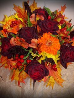 Fall Leaves Bouquet: Black Bacarra Roses, Orange Zinnias, Yellow Alstromeria, Purple Millet, Red Berries, and accented with preserved Oak Leaves.