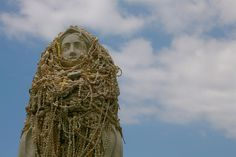 Statuary of the Virgin Mary repleate with gifts of shell rosaries. by Lee Florea, via Flickr