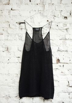 Slinky black strap top against white exposed brick wall - a great back-drop for photos