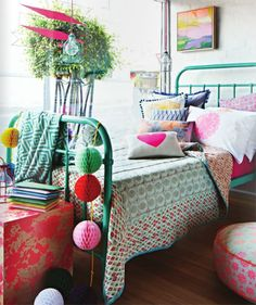 Colorful bed, pom-pom trim pillow, pattern mixing, red and white quilt with blue trim, color scheme.
