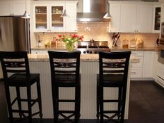 A neutral ceramic tile backsplash, white cabinets and a granite countertop give this kitchen an on-trend update.