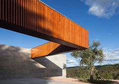 Portuguese architect Duarte Pape combined a long stone wall with folding timber facades in this residential extension.