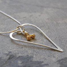 This stunning silver wire heart necklace is delicately accentuated by the overlaying of two golden drops. #Otisjaxon #Jewellery #heart #Women #Giftforher #Accessories