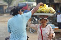 In this photo a Khmer lady is carrying fruit on her head in a delicate balancing act while simultaneously making a sale to a man in Battambang, Cambodia. Battambang Cambodia, Cambodia Travel, Siem Reap, Phnom Penh, Angkor, Travel Photos, Travel Inspiration, Fruit, Lady