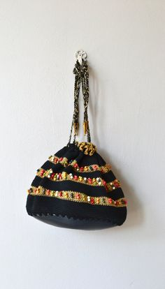 Vintage 1930s black cotton crochet corde handbag with multi-color beading, drawstring closure, stamped silver metal tips and rigid black plastic base, much like a shell. --- M E A S U R E M E N T S --- 9 x 9 6.5 tall maker/brand: n/a condition: excellent ➸ More vintage bags http://www.etsy.com/shop/DearGolden?section_id=10308208 ➸ Visit the shop http://www.DearGolden.etsy.com _____________________ ➸ instagram | deargolden ➸ twitter | deargolden...