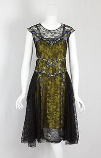 Chantilly lace flapper dress, c.1925. The torso is straight to the drop waist. The skirt, straight in front and full in back, has layers of bias-cut panels. The slip is skillfully constructed with a sheer layer of black silk chiffon over a chartreuse satin lining