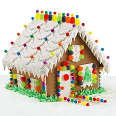 Charming Cottage Gingerbread House - What a welcoming, cozy little cottage. Zigzag icing snow designs on roof topped with candy and punctuated with festive icicles. A dream house trimmed with bright and tempting candies and borders with green leaf trees.