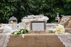 Welcome table with burlap, lace, favors, frame with wedding invitation and wooden mr & mrs sign.