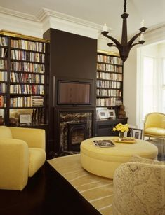 Stylish, light and very welcoming, love the yellow and dark tones in this library - and the neat way they've integrated the fireplace.