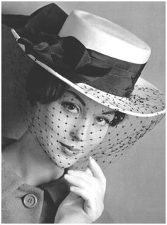 Model is wearing white gros-grain boater with black taffeta band and sheer voilette by Albouy, photo by Philippe Pottier, 1959