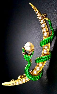 A glistening, slithery green enameled serpent, with a tasty, not too bite-sized, shimmering natural pearl on its tongue, is coiled around a pearl studded crescent moon in this dramatic and unusual Victorian-era pin crafted in 14 karat gold. Just shy of 2 inches long by about 5/8 inch high