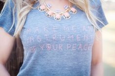 MAKE ME AN INSTRUMENT OF YOUR PEACE Flowy Tee A line taken straight from one of our all-time favorites, The Prayer of Saint Francis, this call to action captures the spirit of Saint Francis who believed in living peacefully and loving one another.