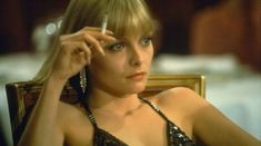 Scarface, directed by Brian De Palma and written by Oliver Stone. Cast: Al Pacino, Mary Elizabeth Mastrantonio, Steven Bauer, and Michelle Pfeiffer. Elvira Hancock, Michelle Pfeiffer Scarface, Scarface Quotes, Scarface Movie, Elvira Scarface, Top Image, Al Pacino, Women Smoking, Movies