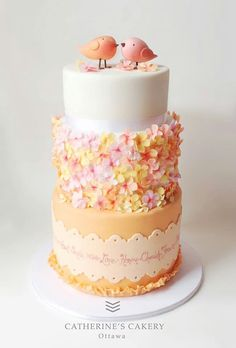 Wedding Cake - two sweet love birds on a tall light coral and white wedding cakes with flower blossom clusters