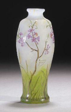 AN ART NOUVEAU DAUM ENAMELLED GLASS VASE. The clear glass internally mottled with white, yellow and green towards the base, etched and enamelled in shades of green, brown and pink with flowers, cameo mark Daum Nancy with a cross of Lorraine.
