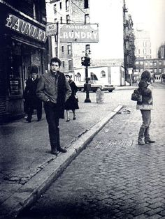 Mr. Bob Dylan waiting on a street in Greenwich Village, New York in 1962. The young woman in the street is his then girlfriend, Ms. Suze Rotolo.