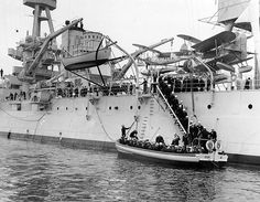Midshipmen and sailors boarding a 50-foot motor launch from battleship USS New York, during the summer 1940 US Naval Academy Midshipmen's cruise; note SOC-3 Seagull floatplanes of Observation Squadron Five onboard. (US Naval History and Heritage Command)