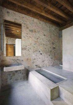 The bathroom in El Badiu features original stone walls with a new concrete tub.