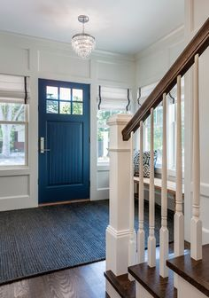 Lovely entry features blue beadboard door flanked by windows dressed in white roman shades