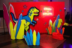 An oversize dinosaur prop and coordinating set pieces decorated a photo booth for Coach.