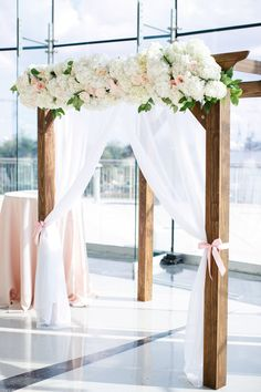 Courtney Inghram Events and Floral Design Virginia-Based Wedding Florist Wedding Flower Arch for Wedding Ceremony at Half Moone in Norfolk, Virginia. Wedding Florist, with Tara Liebeck Photography. Pink, Blush and White, Wedding Color Palette and Flowers with Gold Chivari Chairs and accents. Flower arbor and wooden wedding ceremony arch.