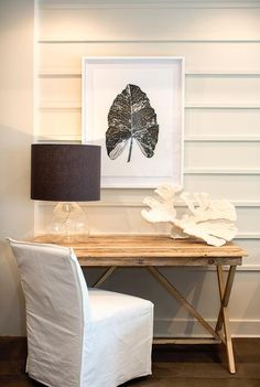 A white slipper desk chair sits in front of a salvaged wood desk topped with a glass tear drop lamp accented with a black shade complementing a white framed black and white foliage print mounted on a shiplap wall.