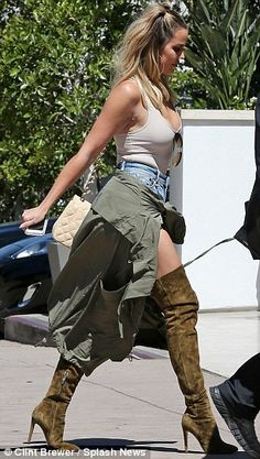 Casual: For her day out, Khloe tucked a low-cut tank top into a pair of distressed, high waist shorts