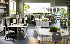 An open-plan office with white desks, drawer units on castors in different heights and widths combined with high-back swivel chairs with beige cover.