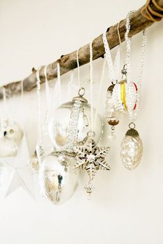 like the idea of hanging baubles etc from a horizontal branch suspended over fireplace or something