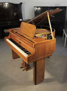 A 1939, Art Deco Allison baby grand piano with a polished satinwood case. Legs and lyre feature strong geometric styling at Besbrode Pianos £3500. Piano has an eighty-five note keyboard and a two-pedal lyre.