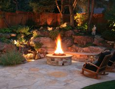The stone patio and fire pit are complimented by the landscape and water feature lighting, allowing this yard to be enjoyed year-round. By Native Edge Landscapes in Boulder, Colorado.