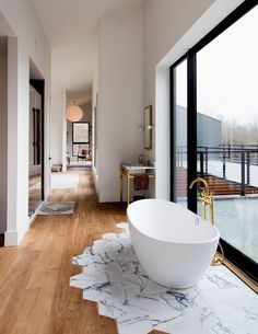A freestanding tub in the master bathroom sits on hexagonal marble tiles inset in the walnut floor. / (Photo: Preston Schlebusch for The New York Times)