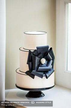 #Ivory fondant cake with a #black sugar bow highlighted with a jeweled #button. #graceormonde #weddingstyle #GOWS #weddingcake #dessert #couture #bride #weddinginspiration #luxuryweddings