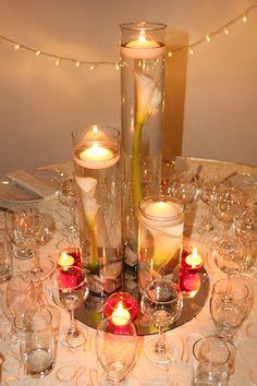 Centro de mesa con cilindros, cartuchos y velas con un toque de color.