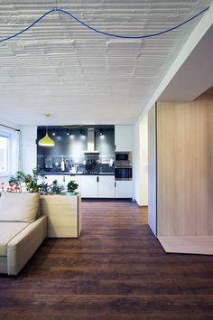 Na podlaze použili lamino, nábytek je vyrobený z OSB desek. Hezky ho doplňují antracitové hrany a antracitové lamino za kuchyňskou linkou; Archiv studia