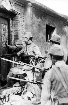 Japanese soldiers break down a door of a house in Shanghai, China.
