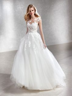 Fabulous ballgown wedding dress with a two-piece effect. A voluminous tulle skirt is combined at the waist with an illusion bodice featuring a detachable lining. A bodice in crystal tulle with Chantilly appliqués, embroidery and beading blends with the skin of the bust and the back, creating a very sexy effect.