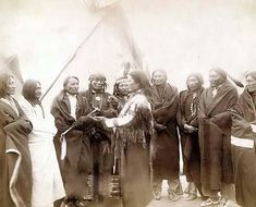Indian chiefs who counciled with General Miles and ended the Indian War -- 1. Standing Bull, 2. Bear Who Looks Back Running [Stands and Looks Back], 3. Has the Big White Horse, 4. White Tail, 5. Liver [or Living] Bear, 6. Little Thunder, 7. Bull Dog, 8. High Hawk, 9. Lame, 10. Eagle Pipe. It was made in 1891 by Grabill, John C. H., photographer.