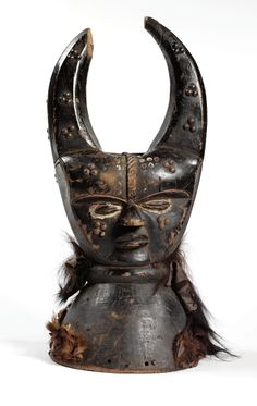 Africa   Janus head crest from the Grebo people of Liberia   Wood, civet fur, brass tacks.  Blackened patina with red and white pigment   ca. 1960