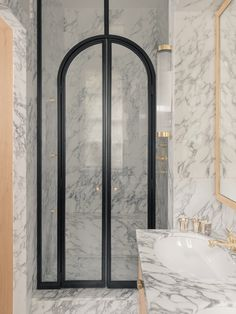 La salle de bains, tout en marbre Arabesacato Poli, a été entièrement conçue sur mesure. Applique (Original BTC), robinetterie (THG), poignées en bronze (Série Rare). Gobelets en argenterie chinés.