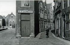 555_12448 Jonge vrouw loopt in de Torenstraat. De huizen links staan in de Wijngaardstraat; … - Regionaal Archief Dordrecht